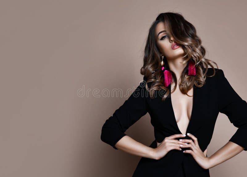 Ung sinnlig härlig sexig kvinna som poserar i det svarta omslaget för mode som är naket på varm beiga arkivfoto