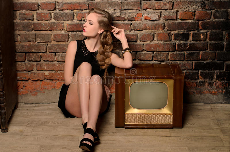 Ung sinnlig kvinna som sitter nära retro tvuppsättning royaltyfri foto
