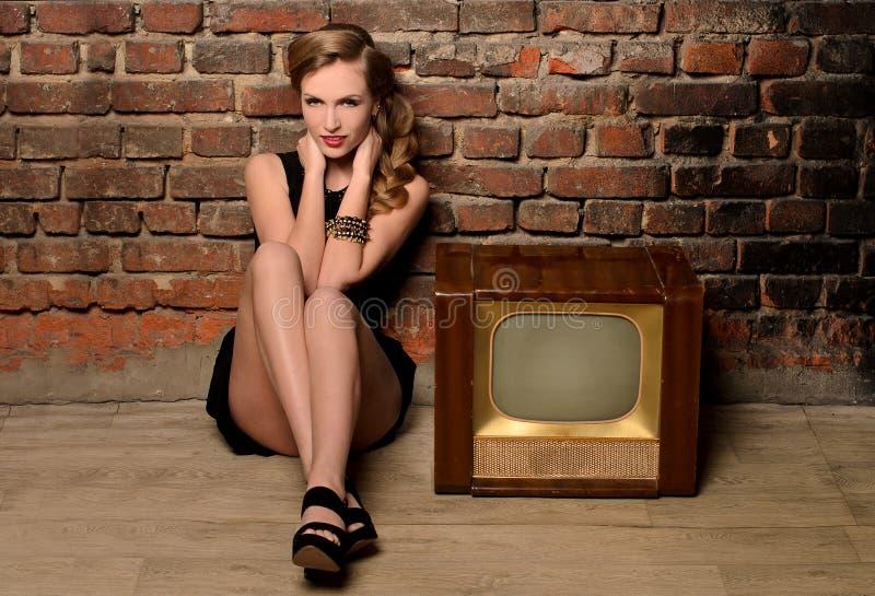 Ung sinnlig kvinna som sitter nära retro tvuppsättning royaltyfri bild