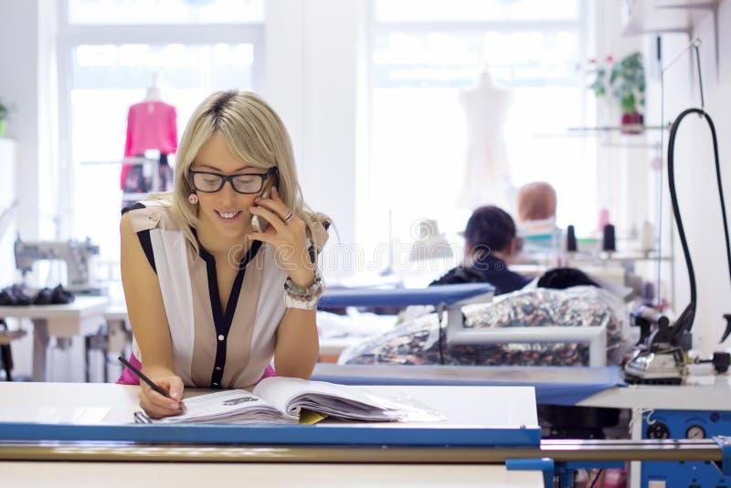 Ung självständig kvinna som tar beställningar vid telefonen arkivbild