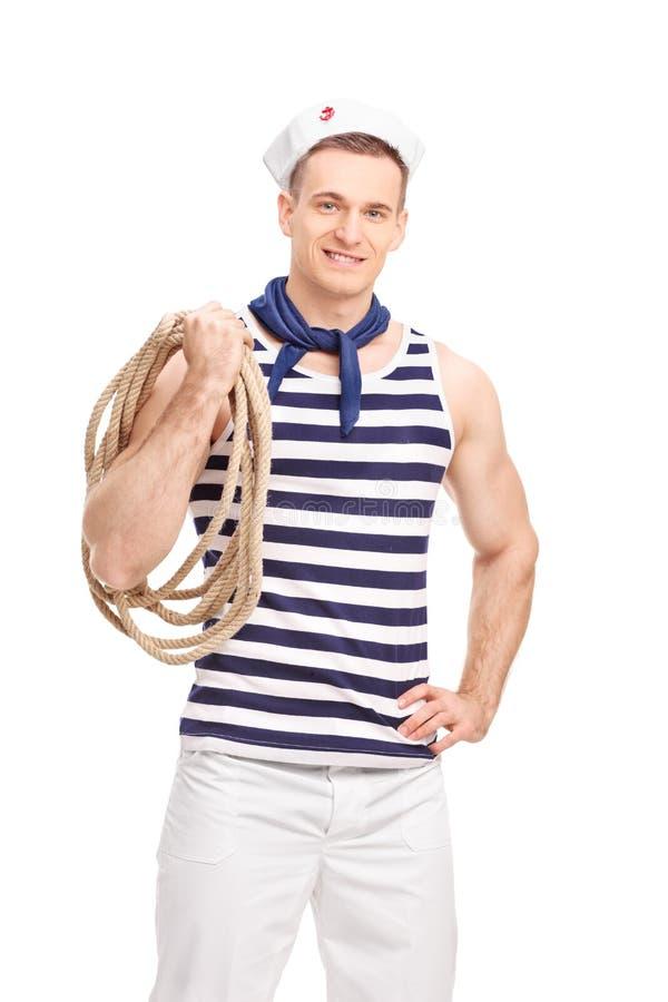 Ung sjöman i en randig skjorta som rymmer ett rep arkivbilder
