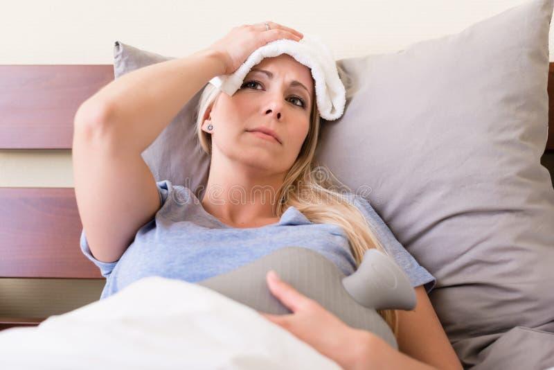 Ung sjuk kvinna med feber som ligger i säng royaltyfria bilder