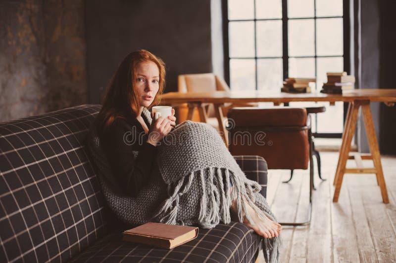 Ung sjuk kvinna som läker med den varma drinken som är hemmastadd på den hemtrevliga soffan arkivbilder