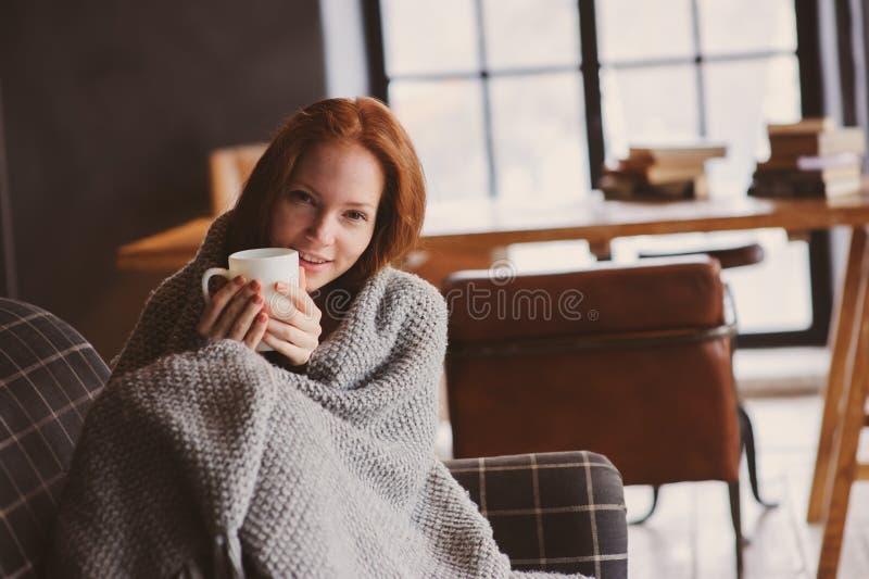 Ung sjuk kvinna som läker med den varma drinken som är hemmastadd på den hemtrevliga soffan arkivbild