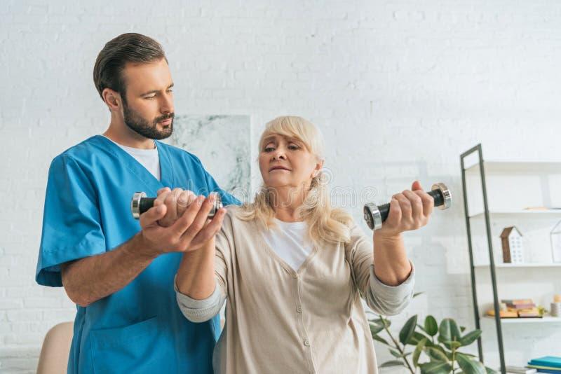 ung sjukskötare som hjälper den höga kvinnan arkivbild