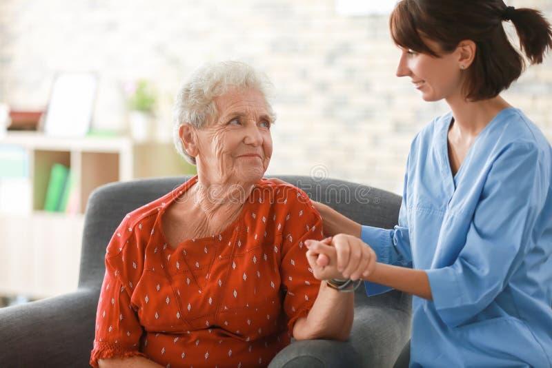 Ung sjuksköterska som hemma besöker den äldre kvinnan arkivbild