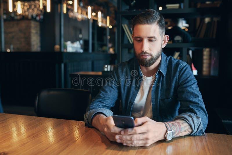Ung skäggig affärsman som är iklädda en grov bomullstvillskjorta och att sitta på tabellen i kafé och brukssmartphone Man som anv royaltyfri bild