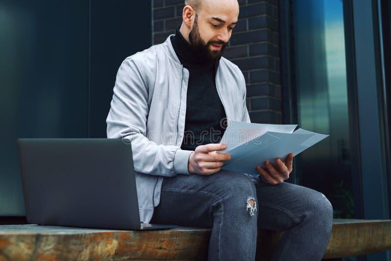 Ung skäggig affärsman som arbetar på bärbara datorn, medan sitta på bänk utomhus Mannen rymmer pappers- dokument i hans händer li arkivfoto