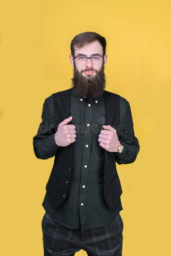 Ung skäggig hipsterman som poserar i studio arkivbilder