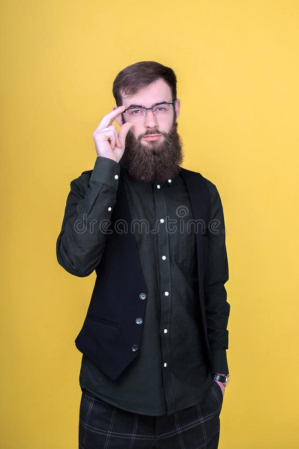 Ung skäggig hipsterman som poserar i studio arkivbild