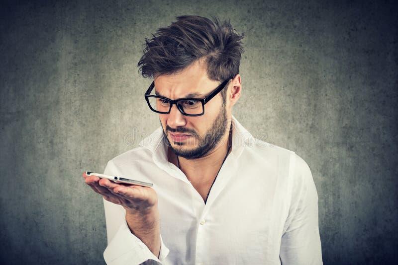 Ung skäggig man i skjortainnehavsmartphonen som den är uppriven med stämmakommandofunktion arkivfoto
