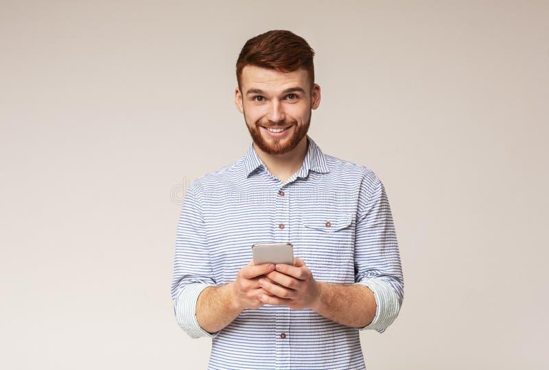Ung skäggig man som använder hans telefon och le royaltyfri bild