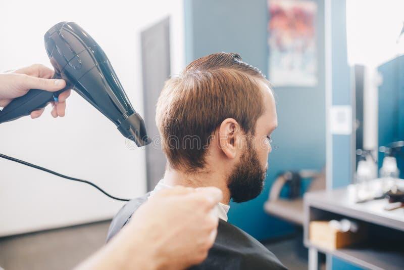 Ung skäggig man som får den ansade frisören med torrare frisersalong för hår Yrkesmässig frisör Drying Hair Handsome arkivbild