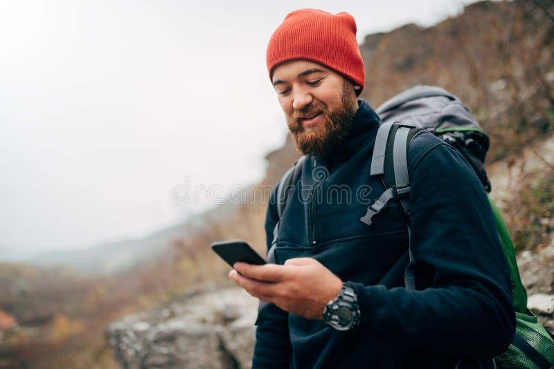 Ung skäggig man som ler och överför meddelanden för hans familj från hans mobiltelefon, under att fotvandra i berg arkivbilder