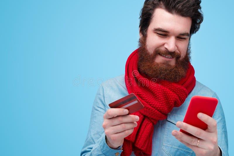 Ung skäggig man som rymmer den plast- kreditkorten och telefonen royaltyfria foton