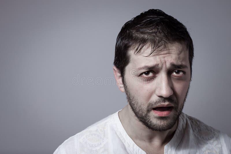 Ung skäggig man som ser sjuk arkivfoto