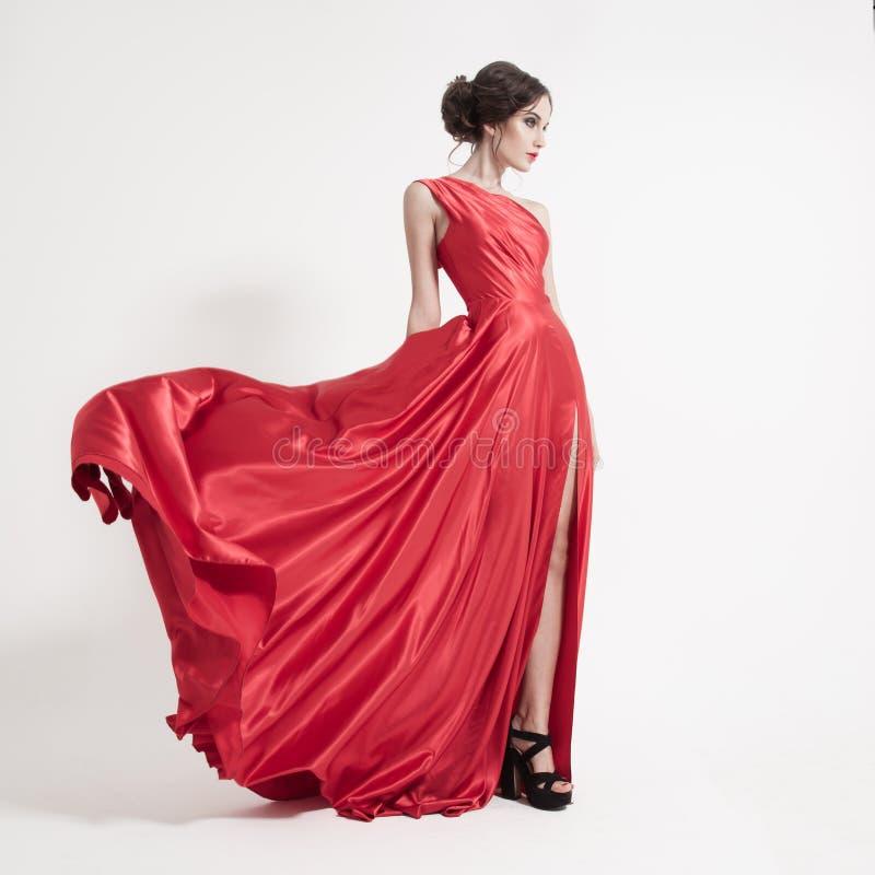 Ung skönhetkvinna, i att fladdra den röda klänningen. Vit bakgrund. royaltyfri bild