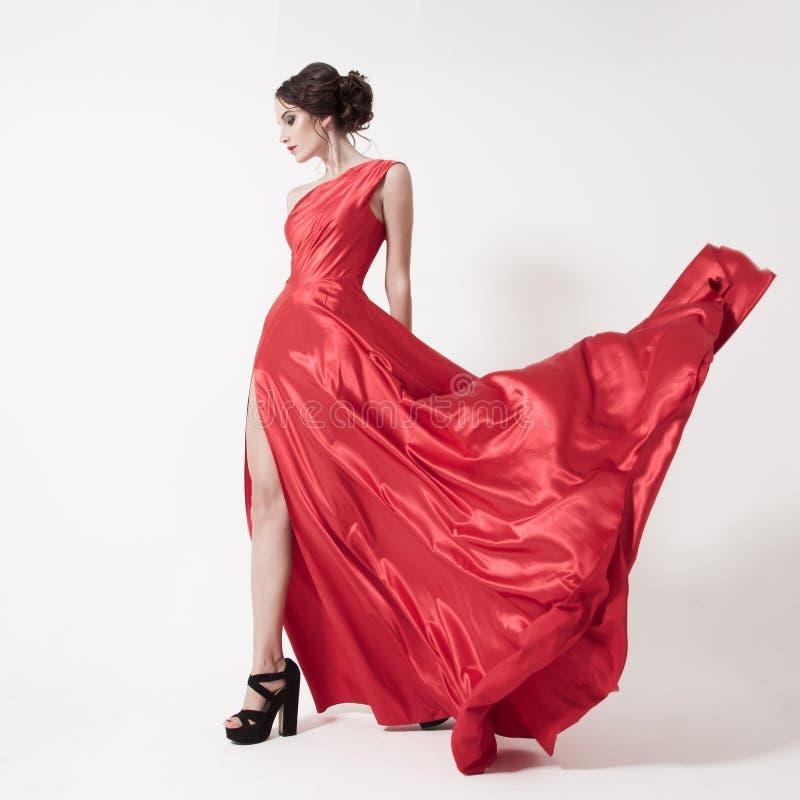 Ung skönhetkvinna, i att fladdra den röda klänningen. Vit bakgrund. arkivbild
