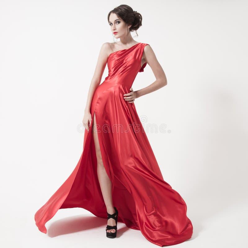 Ung skönhetkvinna, i att fladdra den röda klänningen. Vit bakgrund. royaltyfri foto