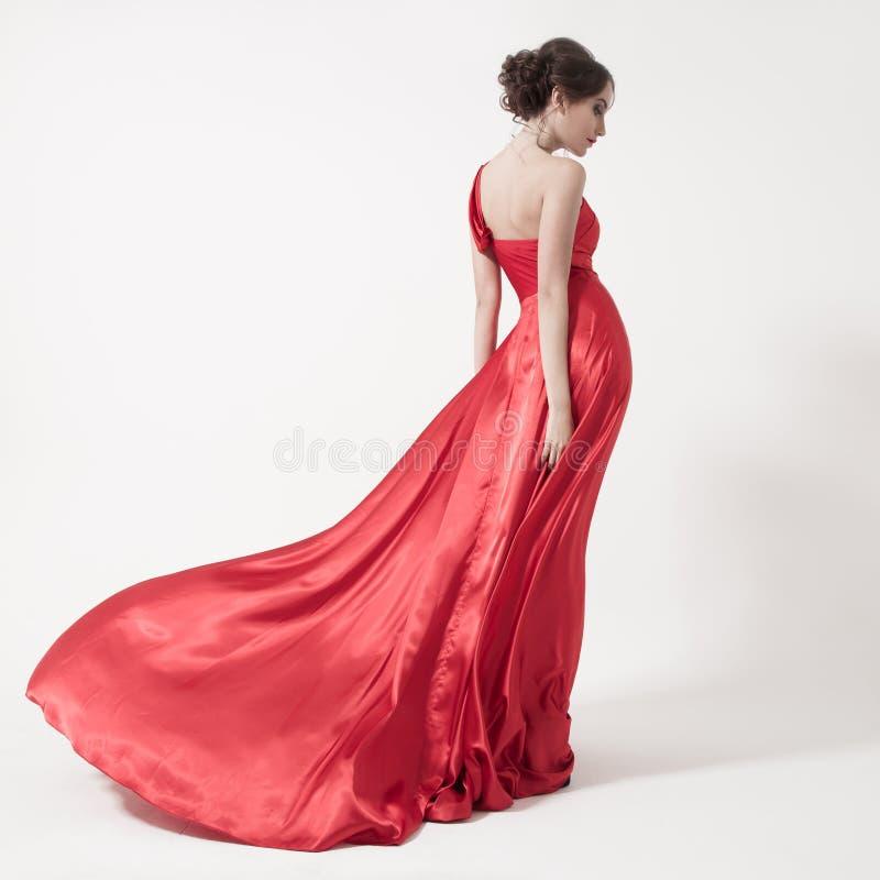 Ung skönhetkvinna, i att fladdra den röda klänningen. Vit bakgrund. royaltyfria bilder