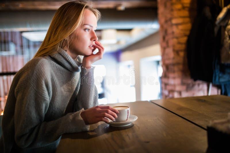 Ung skönhetkvinna i ett kafé som dricker kaffe arkivfoto