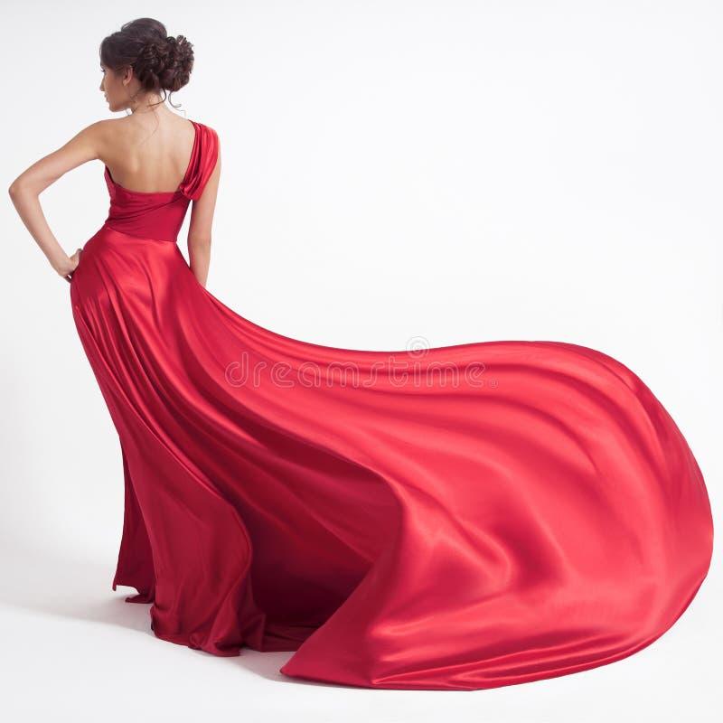 Ung skönhetkvinna i fladdrande röd klänning Vit bakgrund royaltyfria foton