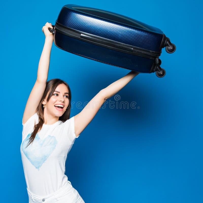 Ung skönhetkvinna med lyftta över huvudet upphetsade sinnesrörelser för bagage som är lyckliga och som är klara för lopp på blå b arkivbilder
