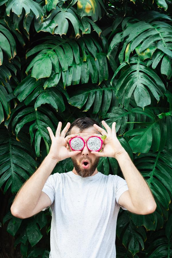 Ung sk?ggig man som framme rymmer skivor av Pitaya drakefrukt av hans ?gon, f?rv?nat royaltyfria foton