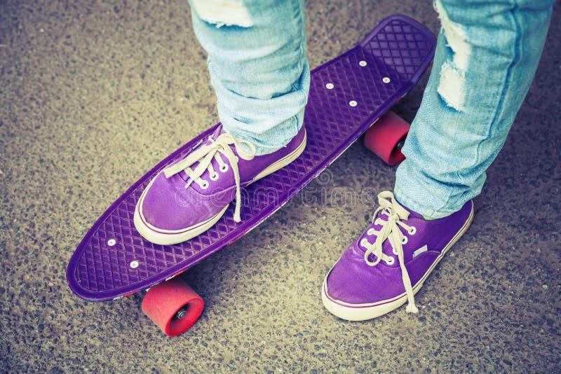 Ung skateboarder i deckare och jeans royaltyfri foto
