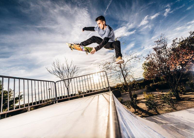 Ung skateboradåkare som gör ett hopp på Skatepark under solnedgång royaltyfria bilder