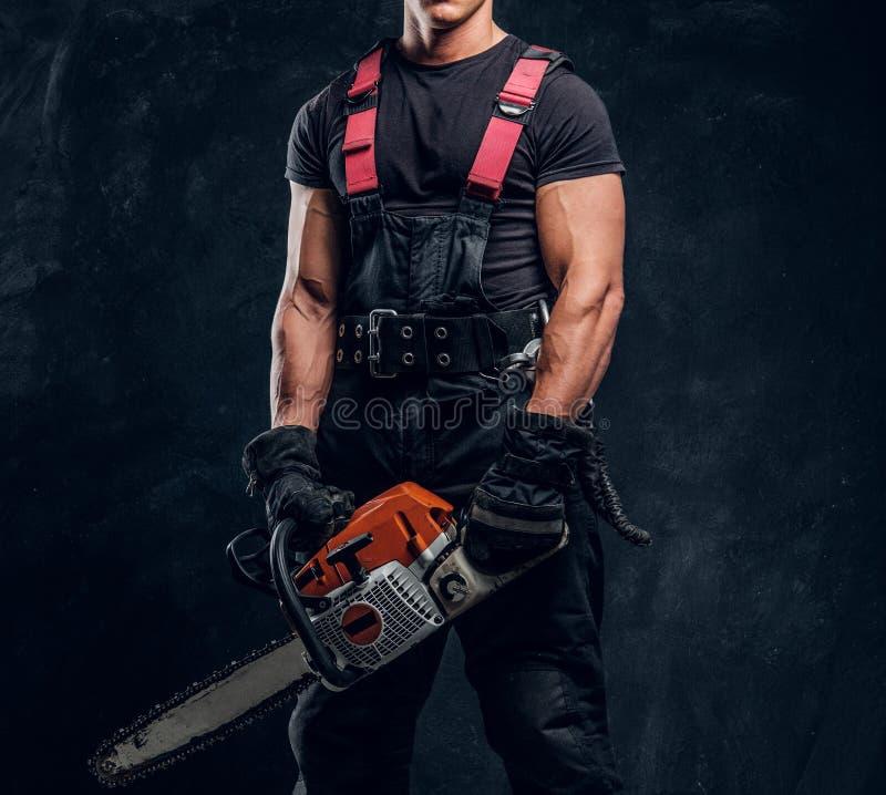 Ung skogsarbetare som bär skyddande kläder som poserar med en chainsaw i en mörk studio fotografering för bildbyråer