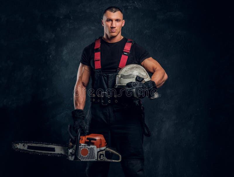 Ung skogsarbetare som bär skyddande kläder som poserar med en chainsaw i en mörk studio royaltyfria bilder