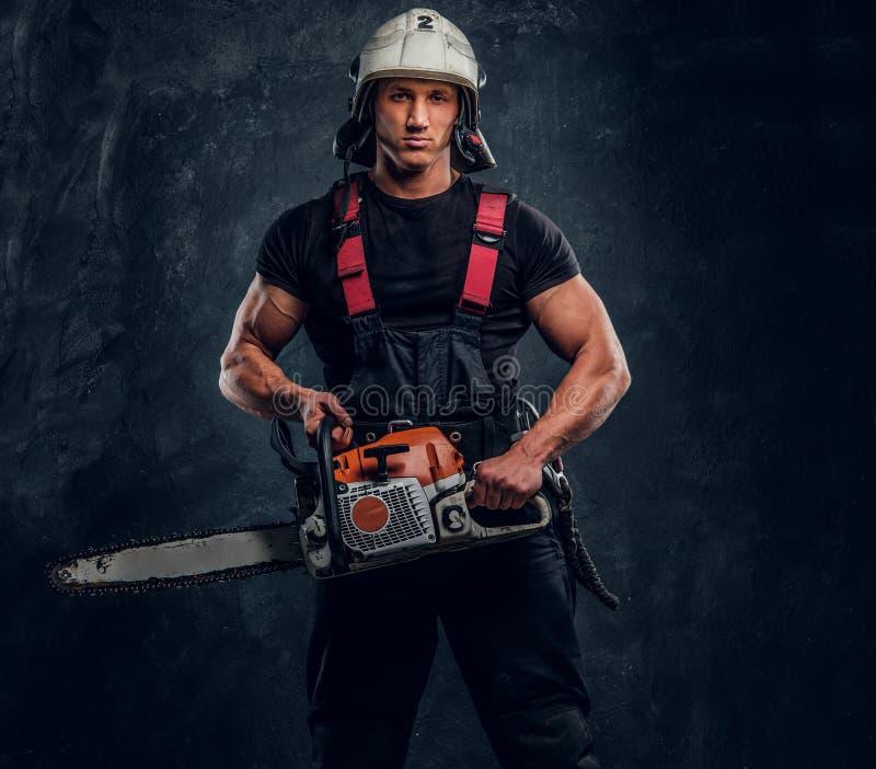 Ung skogsarbetare som bär skyddande kläder som poserar med en chainsaw i en mörk studio arkivfoto