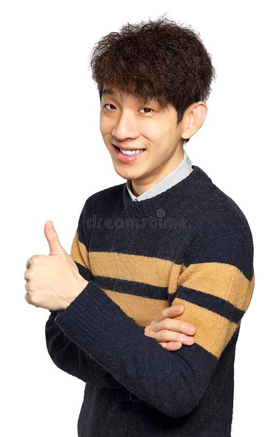 Ung skratta asiatisk manvisningtumme upp handgest arkivfoto