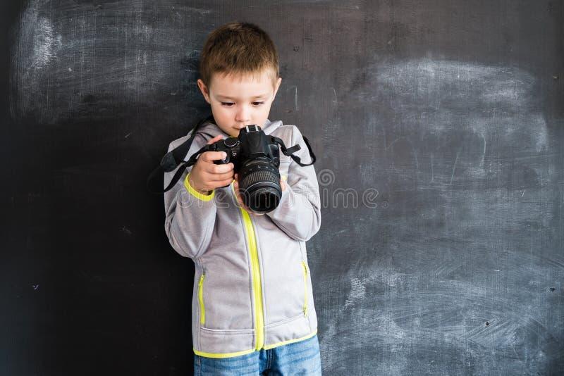 Ung skytte för pojke` s med fotokameran nära svart tavla Ung fotograf Idérikt designbegrepp för kalender 2019 royaltyfri bild