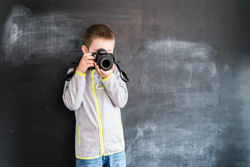 Ung skytte för pojke` s med fotokameran nära svart tavla Ung fotograf Idérikt designbegrepp för kalender 2019 royaltyfria bilder