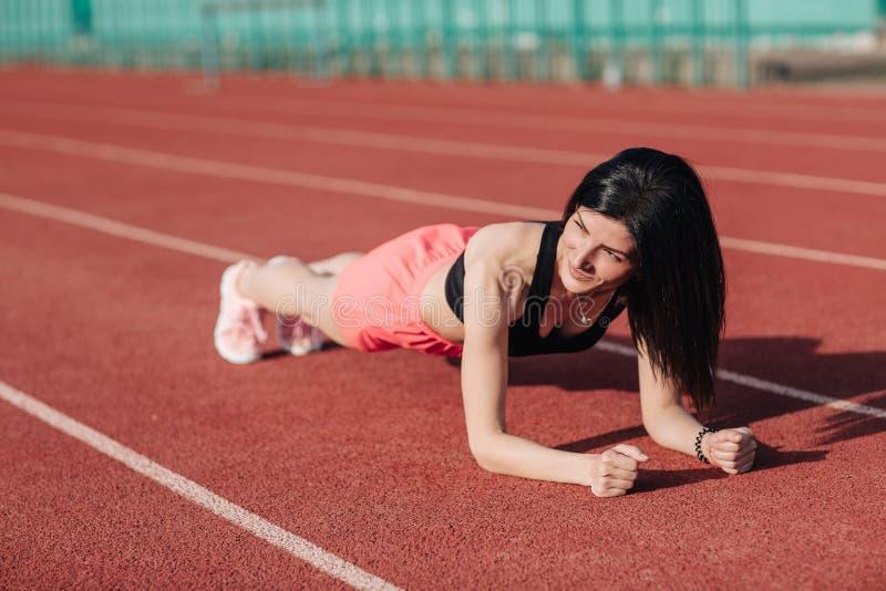 Ung slank attraktiv brunettkvinna i rosa kortslutningar och svart bästa görande plankaövning på utomhus- stadion, kärnautbildning royaltyfria foton