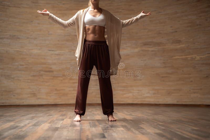 Ung slank dam som står med hennes sideward händer och att meditera royaltyfri fotografi