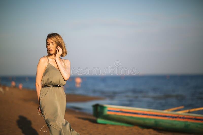 Ung slank flicka som ombord sitter räddningsaktionfartyget på kust arkivbilder