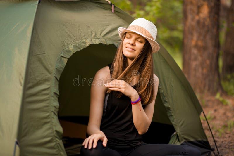 Ung slank fotvandrarekvinna som sitter på det lilla turist- tältet som tycker om den härliga naturskogen royaltyfria foton