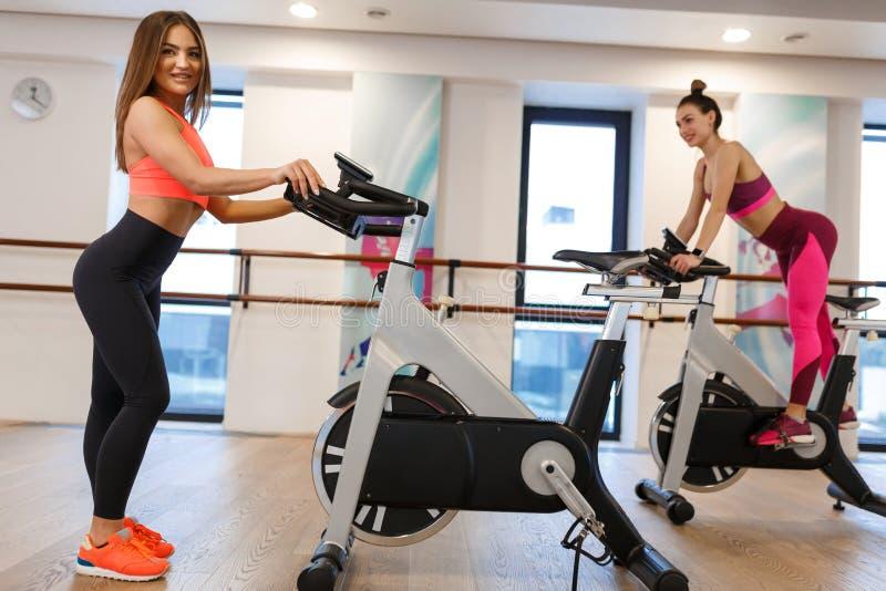 Ung slank kvinna f?r st?ende i sportwearen som poserar p? motionscykelen i idrottshall Sport- och wellnesslivsstilbegrepp royaltyfri fotografi