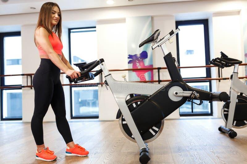Ung slank kvinna f?r st?ende i sportwearen som poserar p? motionscykelen i idrottshall Sport- och wellnesslivsstilbegrepp royaltyfri foto