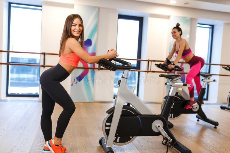 Ung slank kvinna f?r st?ende i sportwearen som poserar p? motionscykelen i idrottshall Sport- och wellnesslivsstilbegrepp arkivfoton