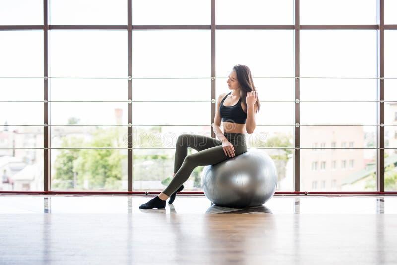 Ung slank kvinna i sportswear som tätt övar hennes abs på en Pilates boll av fitball upp på idrottshallen avkoppling för pilates  fotografering för bildbyråer
