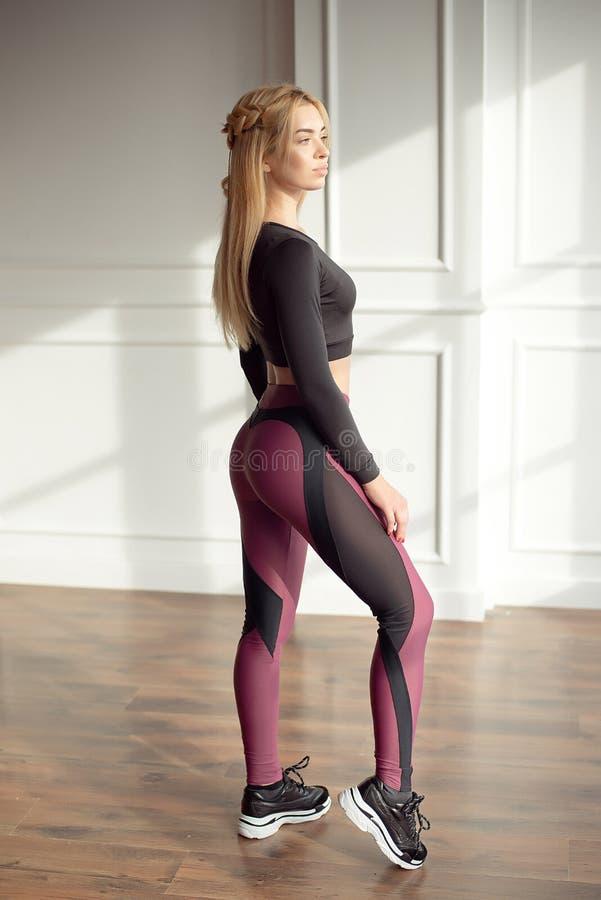 Ung slank kvinna med ett långt blont hår för idrotts- kropp som bär i sportsportswearöverkant, och damasker som står i ljust royaltyfri fotografi