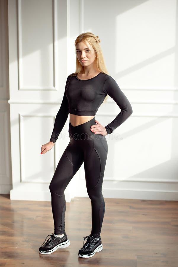 Ung slank kvinna med ett långt blont hår för idrotts- kropp som bär i svart sportsportswearöverkant och damaskeranseende fotografering för bildbyråer