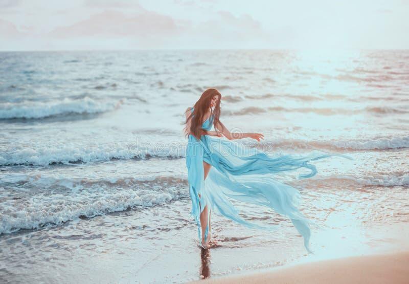Ung slank kvinna med långa ben som dansar på havet royaltyfria bilder