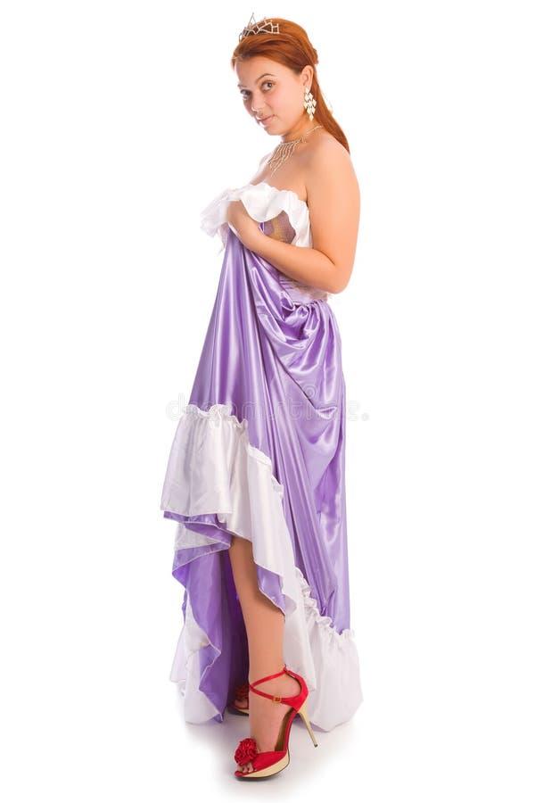 Ung smileykvinna i den långa lila-färgade bollklänningen som isoleras på royaltyfria foton