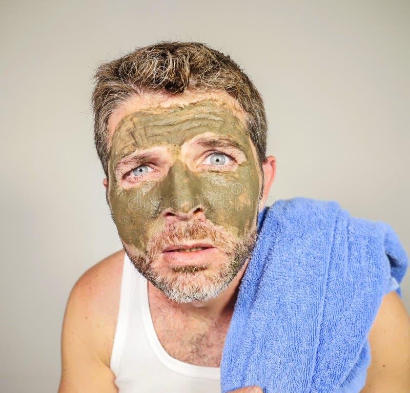 Ung smutsig rolig man som ser honom som förskräckas i badrumspegel med gräsplankräm på hans framsida som applicerar den pro-ansik arkivfoton