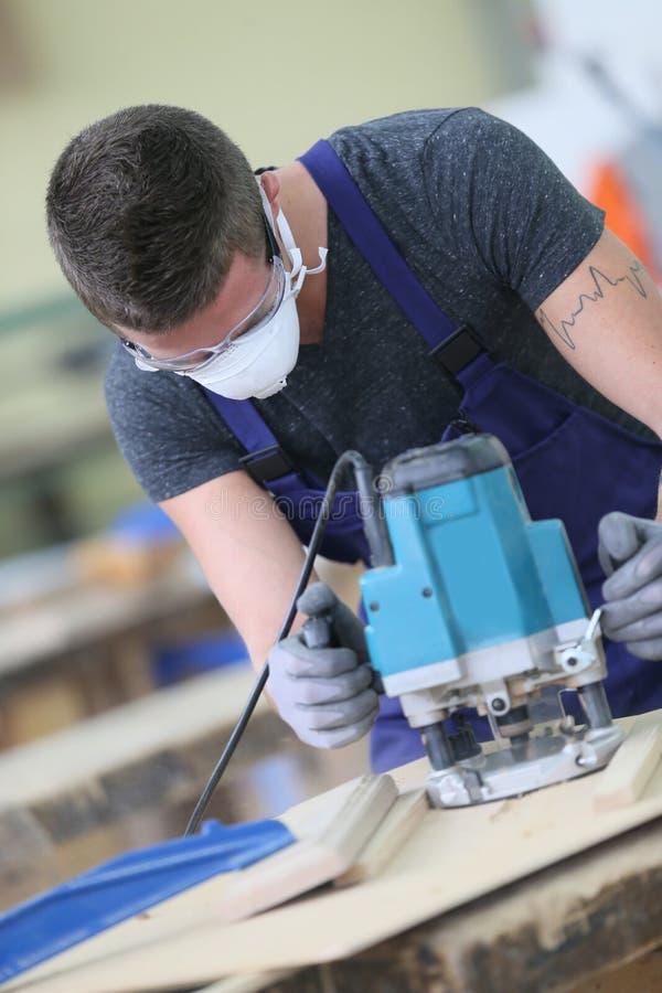 Ung snickarelärling som arbetar på trä arkivbild